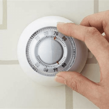 person adjusting a Thermostat