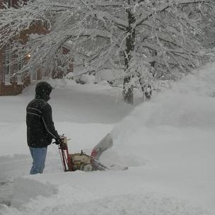 man blowing snow in deep snow