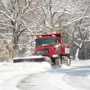Snow Plow in Distance plowing snow on roadway