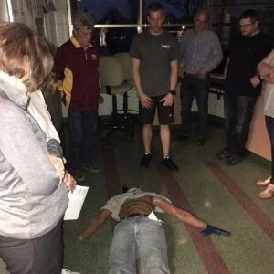 Crime scene of pretend body surrounded by students
