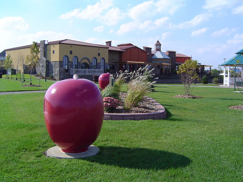 Park with apple sculpture and restaurant in background