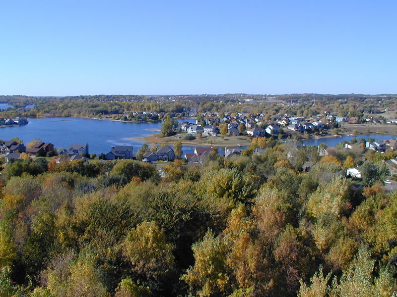 Lake with houses around it and trees in foreground