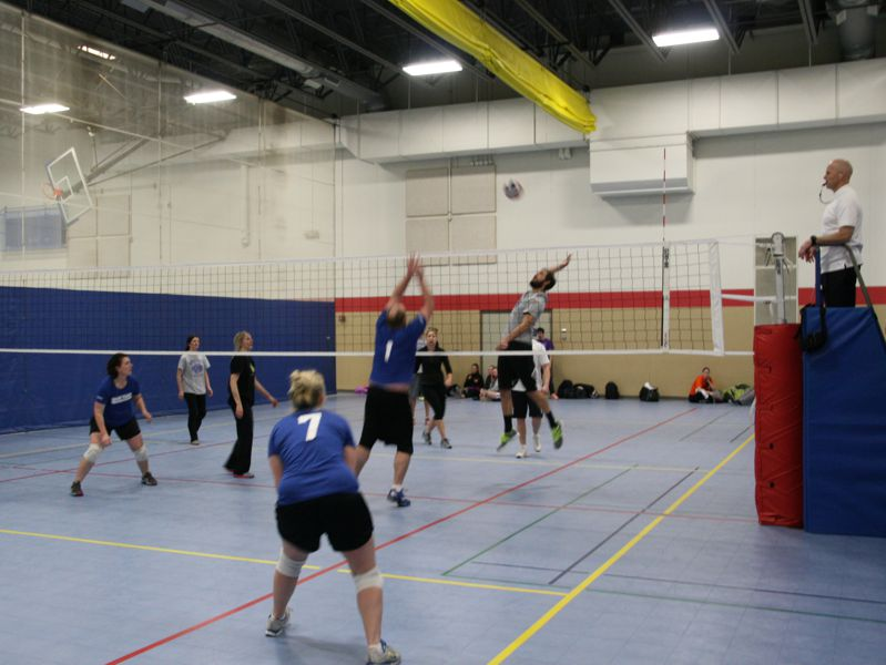 people playing volleyball game in gym